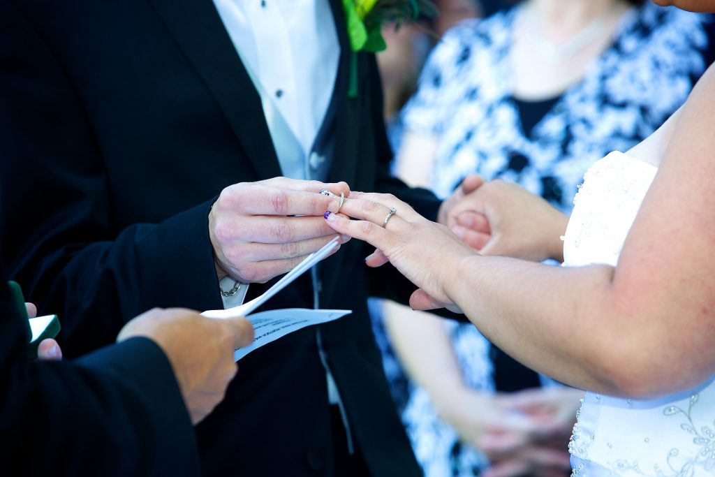 A couple place rings on each other's hands during a wedding.